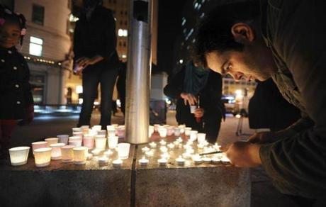Mario Buda lit candles during a vigil in Oakland, Calif.